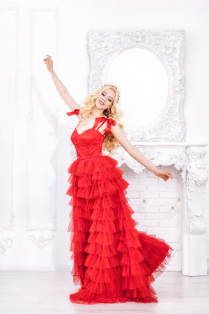 Luxurious young beautiful model blonde woman in a chic red dress and decorations in the interior Imagens