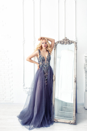 Luxurious young beautiful model blonde woman in a chic long dress in the interior