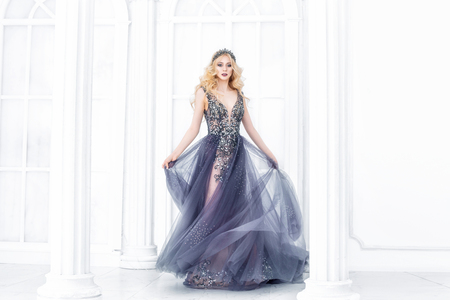 Luxurious young beautiful model blonde woman in a chic long dress and a crown in the interior
