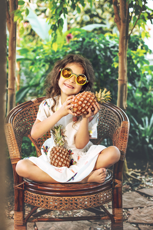 Little beautiful cute baby girl in white dress and sunglasses with pineapples in hands on tropical plants background Imagens