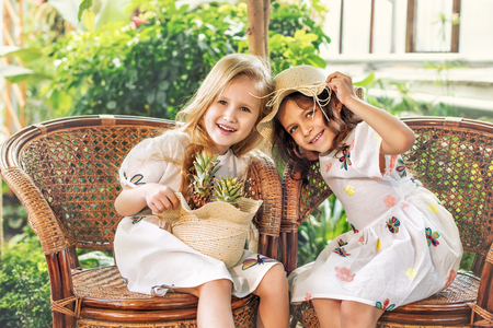 Little beautiful cute girls kids in white dresses with pineapples in hands on tropical plants background Imagens