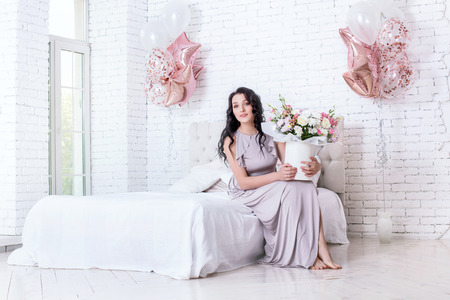Young adult beautiful woman in long fashionable holiday dress with balloons and flowers in white bedroom