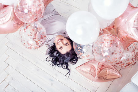 Young adult beautiful woman in fashionable holiday dress with pink balloons lying on white wooden floor top view Standard-Bild