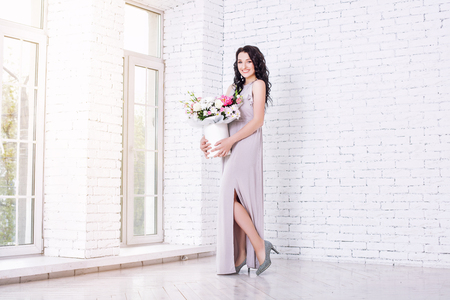 Young adult beautiful woman in a long fashionable festive dress with a bouquet of flowers in a bright interior Imagens