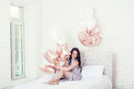 Young adult beautiful woman in long fashionable holiday dress with pink balloons in white bedroom