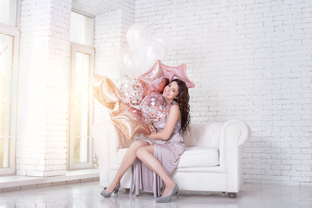 Young adult beautiful woman in a long fashionable festive dress with pink balloons on a white sofa in a light interior