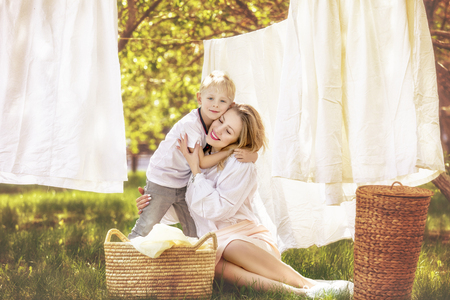 Family mother and son, beautiful and happy together hang clean Laundry in the garden