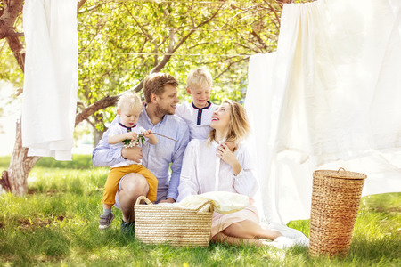 Family father, mother and two sons, beautiful and happy together hang clean Laundry in the garden Imagens
