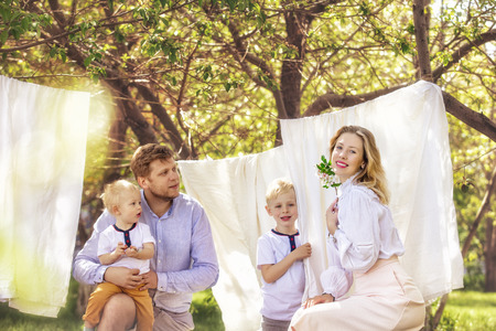 Family father, mother and two sons, beautiful and happy together hang clean Laundry in the garden Reklamní fotografie