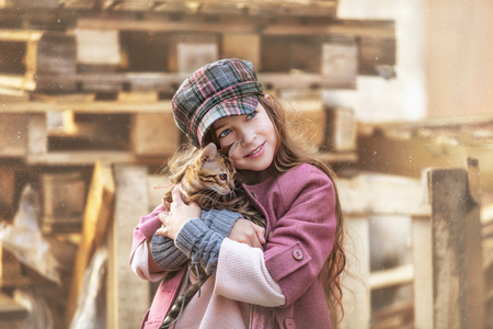 Fashionable child girl beautiful and happy with cute little Bengal kitten together on the street Reklamní fotografie