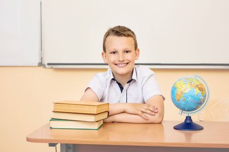 Boy child schoolboy happy, funny and cute with smile - portrait in classroom sitting at Desk