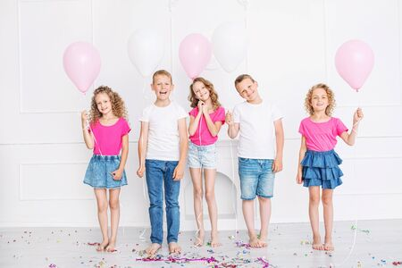 Happy beautiful cute kids smile at the holiday party with balloons and confetti together in the white room Imagens