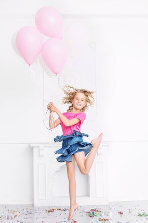 Happy beautiful cute child girl with smile at holiday party with balloons and confetti in white room Imagens