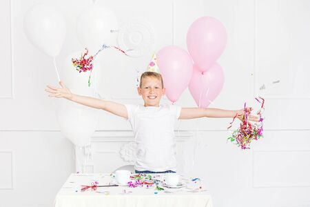 Happy beautiful cute kid boy with smile at holiday party with balloons and confetti in white room Imagens