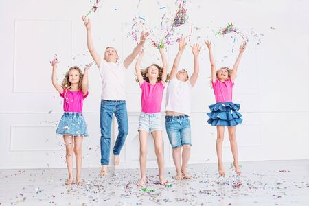 Happy beautiful cute kids smile at the holiday party with confetti together in the white room Imagens