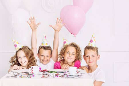Happy beautiful cute kids smile at the holiday party with balloons and confetti together at the table in the white room