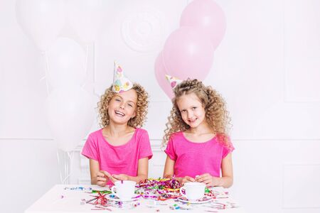 Happy beautiful cute kids two girls smiling at party celebration with confetti together in white room