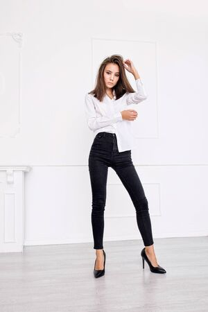 Young beautiful model with natural makeup and beautiful hair on white background in black jeans and white shirt Zdjęcie Seryjne