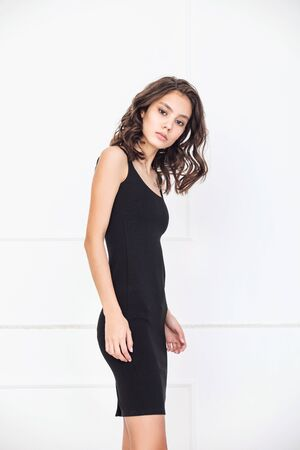 Young beautiful model with natural makeup and beautiful hair on white background in black dress