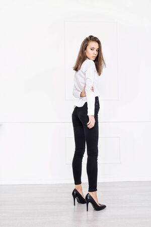 Young beautiful model with natural makeup and beautiful hair on white background in black jeans and white shirt Imagens