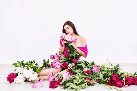 Young beautiful brunette woman model with beautiful makeup and long hair in pink colors - peonies Imagens