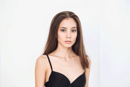 Young beautiful model with natural makeup and beautiful hair on a white background face close-up 스톡 콘텐츠