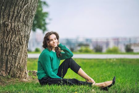 Young beautiful adult girl with natural makeup fashionable and happy resting in the city Park Фото со стока