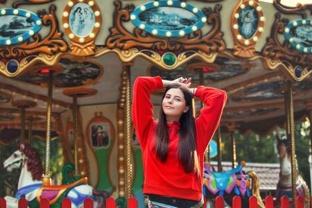 Young beautiful brunette woman happy in the Park on the background of bright colored carousel