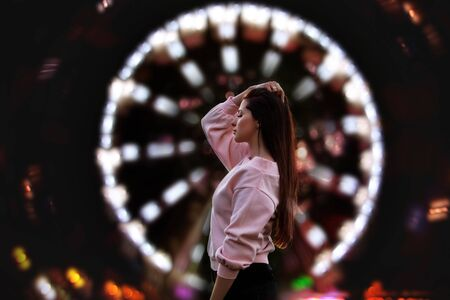 Young beautiful brunette woman happy in the city at night on the background of Park and Ferris wheel