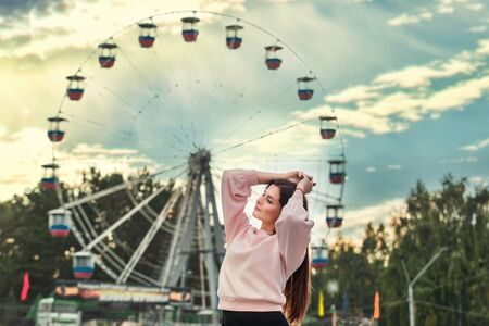 Young beautiful brunette woman happy in the city on the background of Park and Ferris wheel Фото со стока
