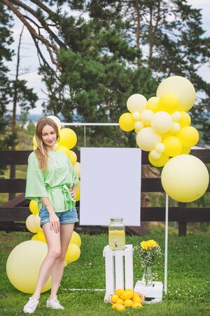 Young adult beautiful blonde girl happy on green grass with balloons and lemonade
