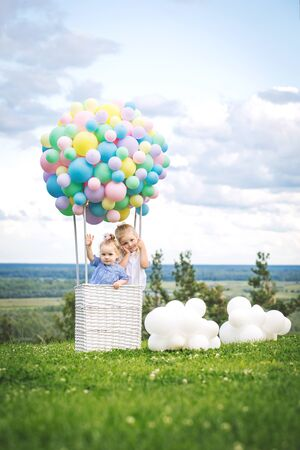 Little cute girls kids beautiful and happy on green grass with balloon airship on blue sky background with clouds