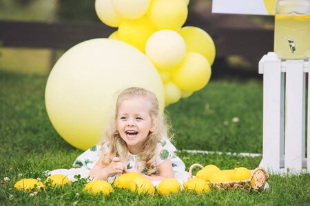 Little cute child girl beautiful and happy on green grass with balloons and lemonade