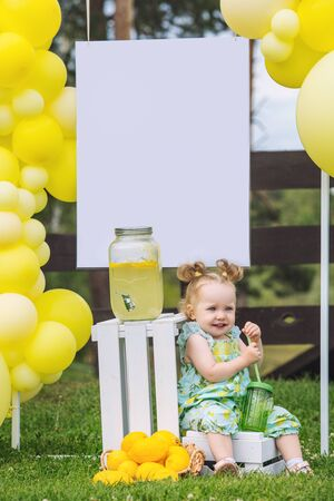 Little cute baby girl beautiful and happy on green grass with balloons and lemonade Фото со стока