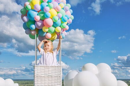 Little cute child girl beautiful and happy on green grass with balloon airship on blue sky background with clouds