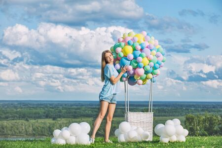 Young adult beautiful blonde girl happy on green grass with balloon airship on blue sky background with clouds