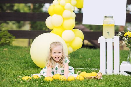 Little cute child girl beautiful and happy on green grass with balloons and lemonade Stockfoto