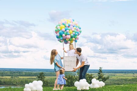 Family mother, father and two daughters beautiful and happy on the green grass with a balloon airship on the background of blue sky with clouds