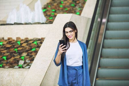 Young adult beautiful brunette girl happy on escalator with mobile phone in hands
