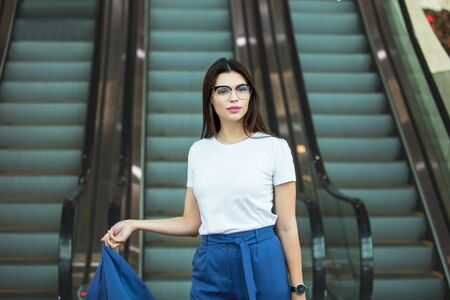 Young adult beautiful brunette girl happy businesswoman on escalator in business center Фото со стока