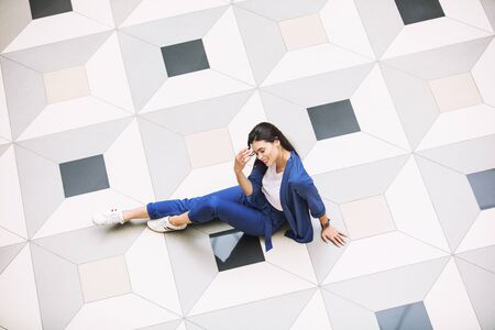 Young adult beautiful brunette girl happy on tile with geometric pattern top view