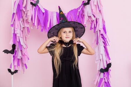 Little beautiful cute child girl in witch carnival costume in fashionable Halloween decorations