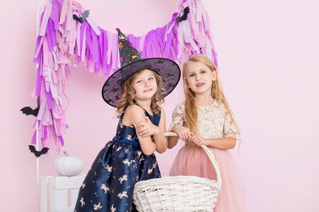 Two little beautiful cute children girls in carnival costumes witches and fairies in fashionable Halloween decorations