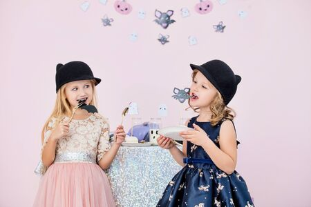 Two little beautiful cute children girls in carnival costumes at a table with sweets and drinks in fashionable Halloween decorations Фото со стока