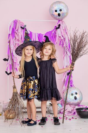 Two little beautiful cute children girls in carnival witch costumes in fashionable Halloween decorations