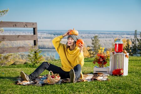Young adult beautiful woman in nature on picnic with plaid, pumpkins and autumn scenery