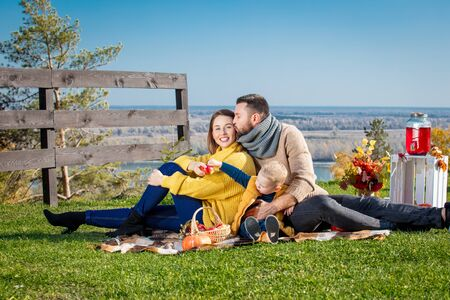 Happy family mother, father and little baby son together in nature on picnic with plaid, pumpkins and autumn decorations