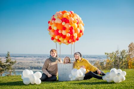Happy family mother, father and daughter together in nature with balloon for air travel