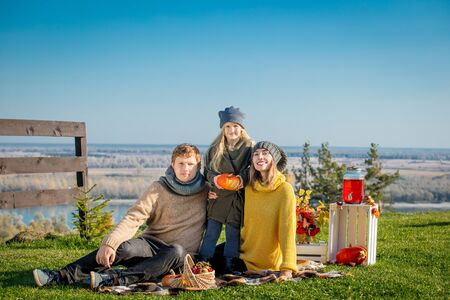 Happy family mother, father and daughter together in nature on picnic with plaid, pumpkins and autumn decorations