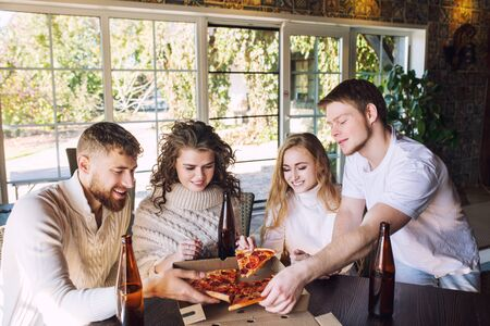 Friends four two men and two women young adults beautiful and happy together at the table eating pizza and drinking drinks from bottles